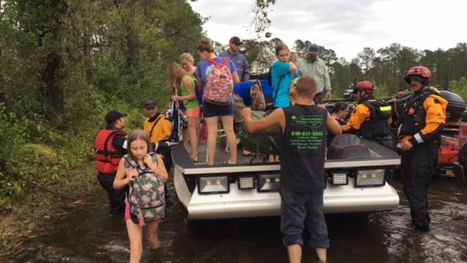 Des sinistrés réunis par les autorités pour être évacués.