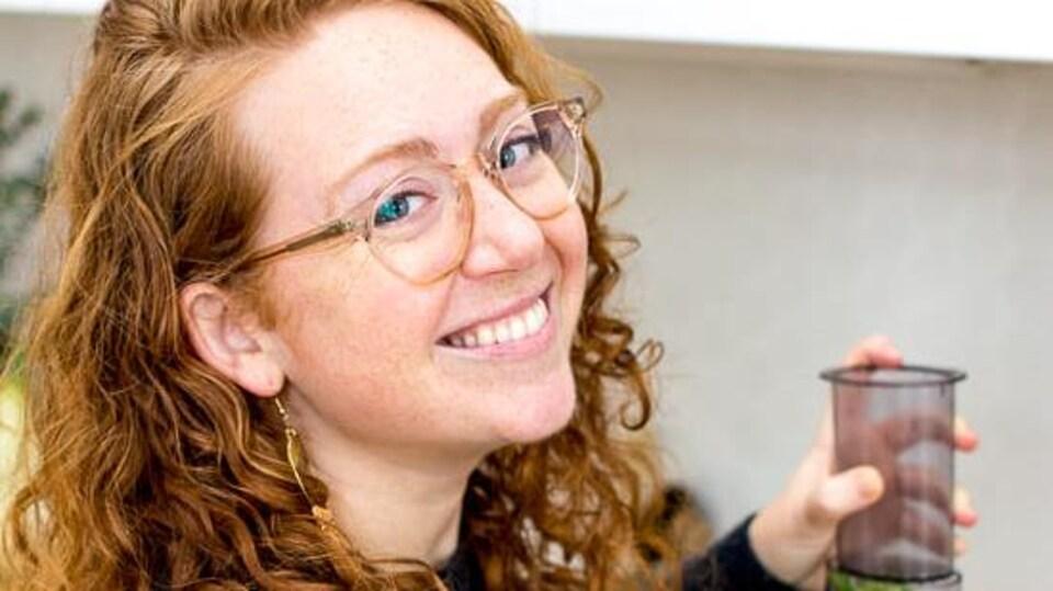 La jeune femme sourit à la caméra. Elle tient un mélangeur qui contient des légumes.