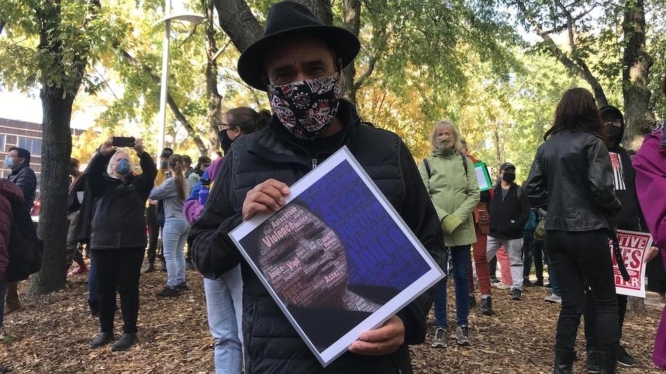 Florent Vollant porte un masque et tient une affiche.