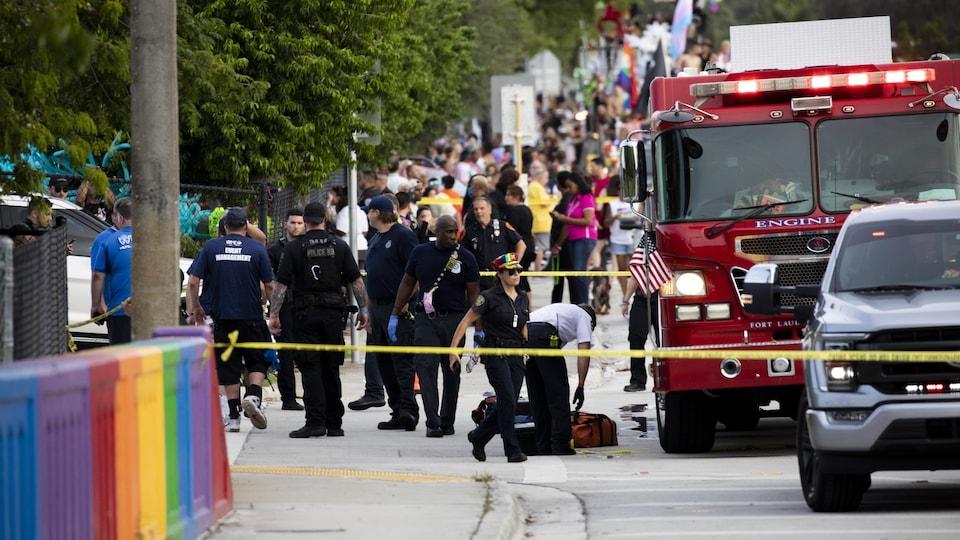 Des policiers et un camion du service incendie dans un décor aux couleurs de la communauté LGBTQ+.