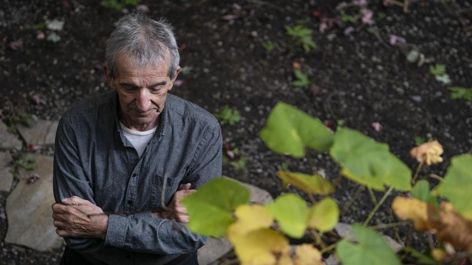 Jacques Cossette-Trudel regarde le sol, les bras en croix.