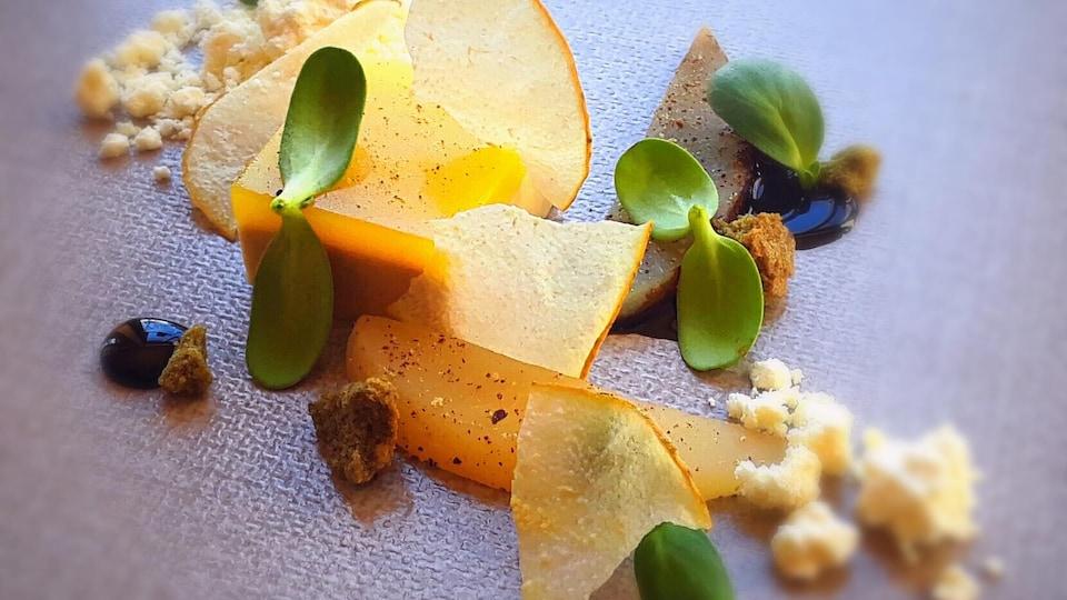 Gros plan sur un plat du restaurant Narval à Rimouski. Rubans de poires avec foie gras, poivre et pousses de tournesol.
