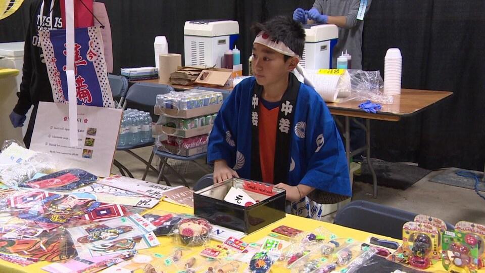 Un garçon d'origine japonaise est debout derrière un kiosque rempli d'objets.