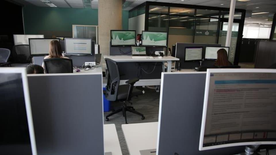Deux personnes devant des ordinateurs dans un bureau du gouvernement fédéral.
