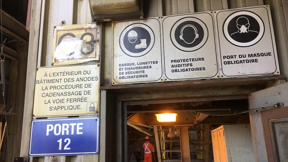 Des pancartes indiquent le port obligatoire du casque, des lunettes, des chaussures, de protecteurs auditifs et du masque.