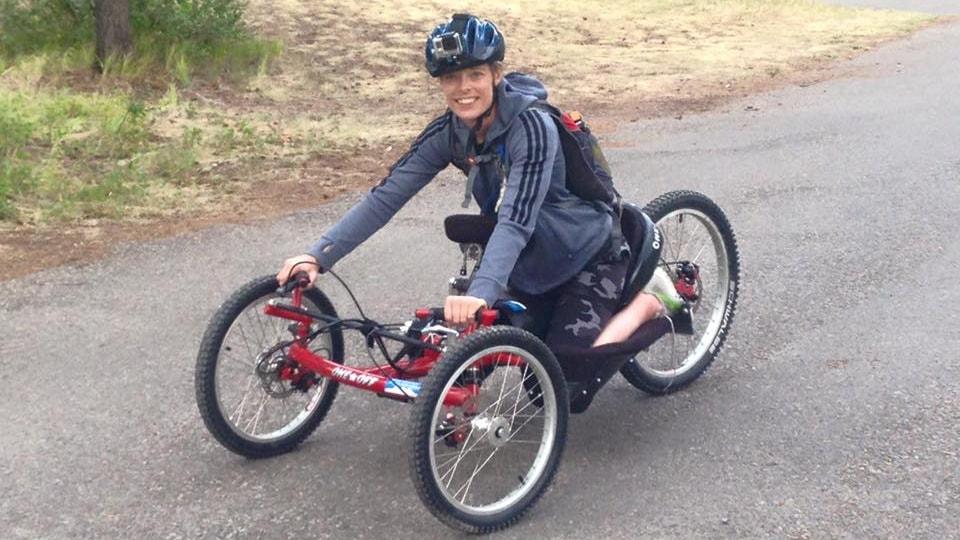 Une jeune femme est assise sur un vélo pour handicapé.