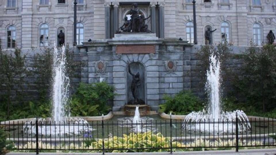 Fontaine avec fleurs et statues représentant une famille abénaquise devant le parlement.