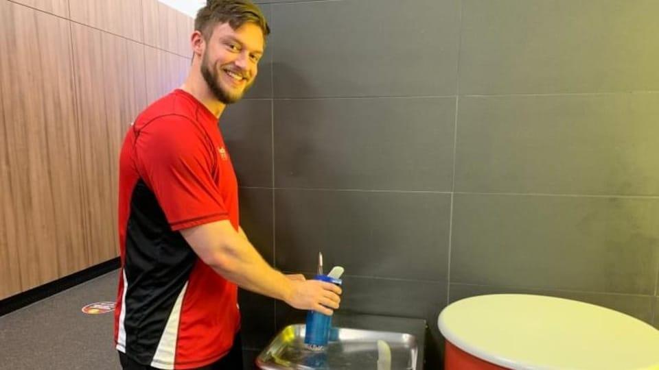 Un homme remplit sa bouteille d'eau à partir d'une fontaine, dans un gymnase.