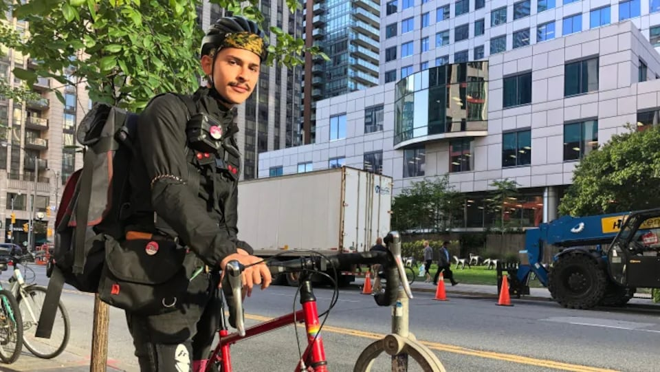 Photo d'un jeune homme qui porte un sac à dos et tient un vélo sur le trottoir.