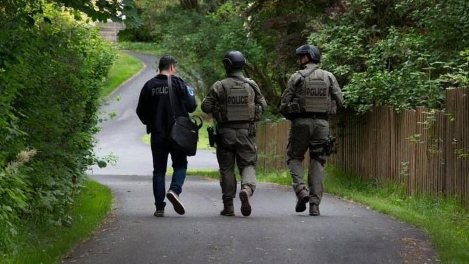 Trois membres de police de dos marchent dans une ruelle.
