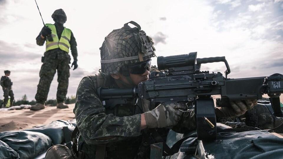 Un soldat équipé tire sous l'oeil d'un autre soldat qui supervise les opérations.