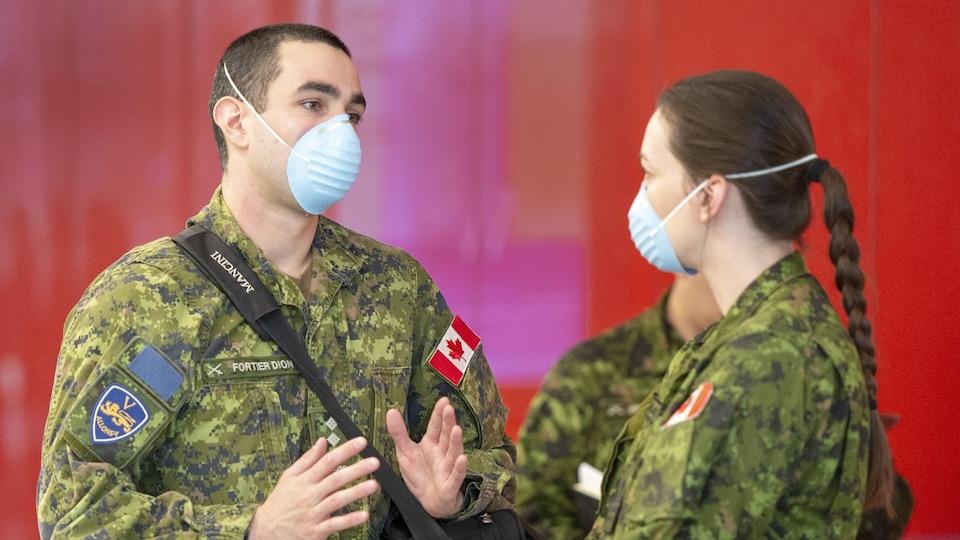 Deux militaires discutent ensemble. Ils portent un masque.
