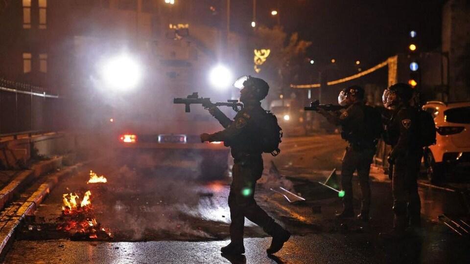 Des membres des forces israéliennes armés traversent une rue où des débris enflammés jonchent le sol.