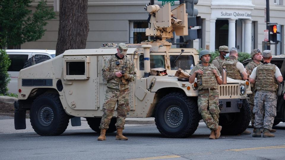Une dizaine de soldats debout autour d'un véhicule militaire.
