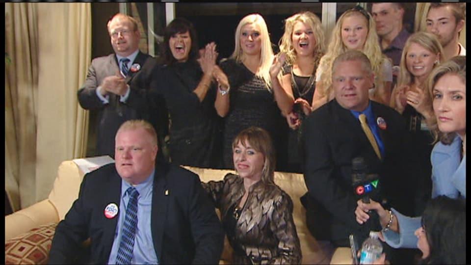 Les deux frères Ford sont assis sur un sofa avec l'épouse de Rob Ford, et plusieurs membres de la famille sont debout en arrière, souriant, applaudissant.
