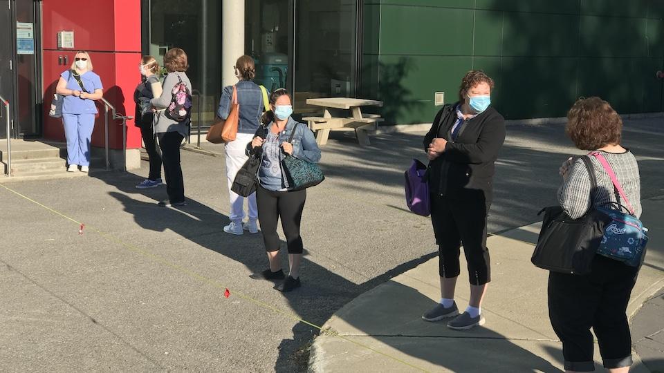 Les premières personnes dans la file pour entrer dans les locaux de formation, lundi matin.