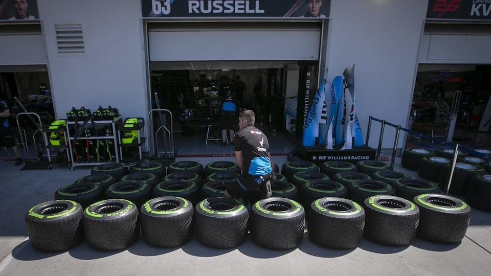 Un employé d'une écurie s'occupe de pneus de voiture de course déposés sur le sol.