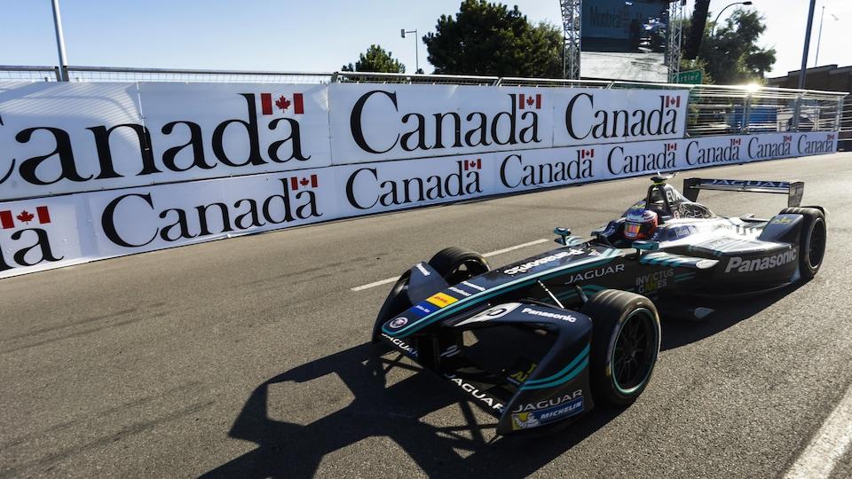 Une Jaguar passe devant des affiches du gouvernement canadien.