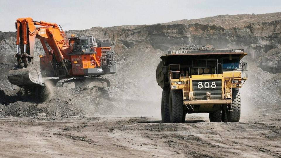 Des camions sur un chantier d'exploitation de sables bitumineux.
