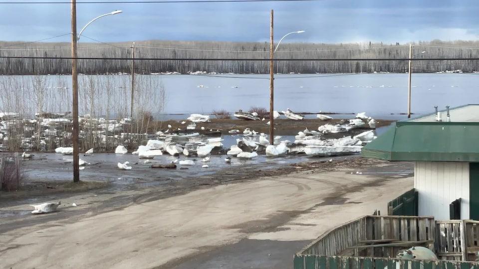 Des blocs de glace sur une route à côté d'un fleuve à Fort Simpson.
