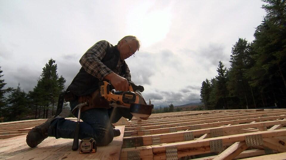 On voit M. Fortier en train de manipuler une scie sur le toit d'une maison en construction.
