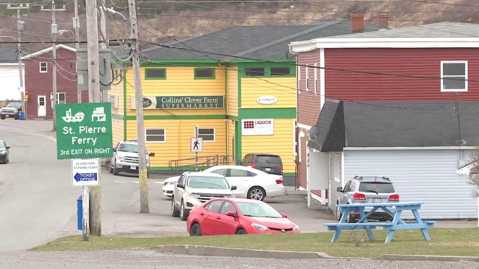 Un bâtiment jaune abritant une épicerie et un magasin d'alcool.