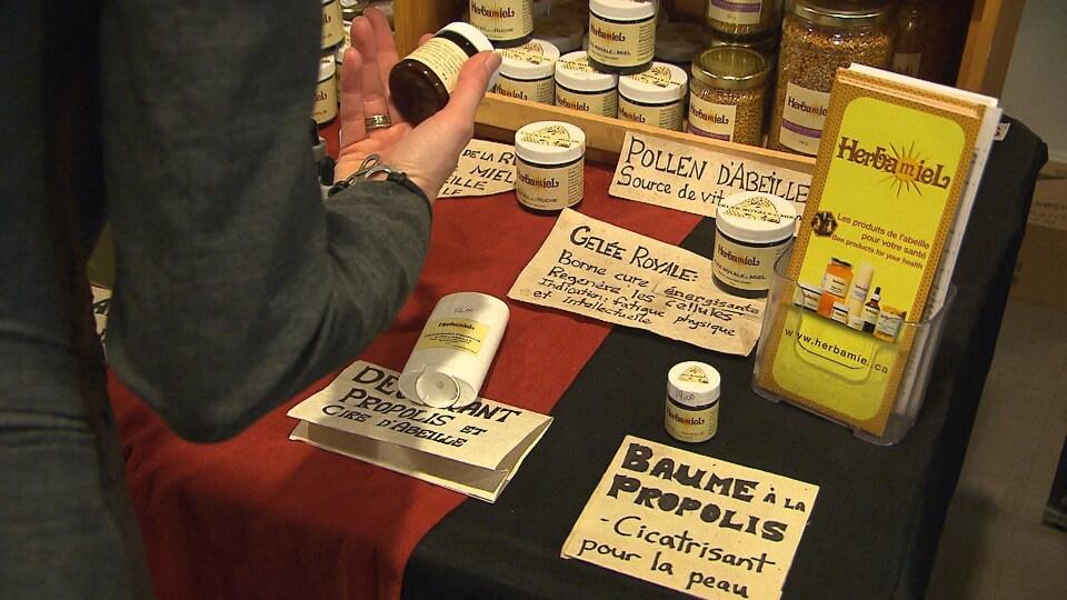 Une table sur laquelle sont présentés plusieurs produits à base de miel, cire d'abeille et gelée royale.