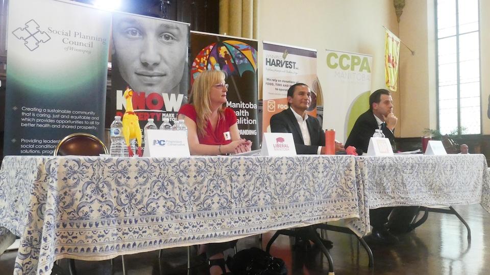 Trois candidats assis à une table, devant une série de panneaux promotionnels d'organismes communautaires, dans une grande salle.