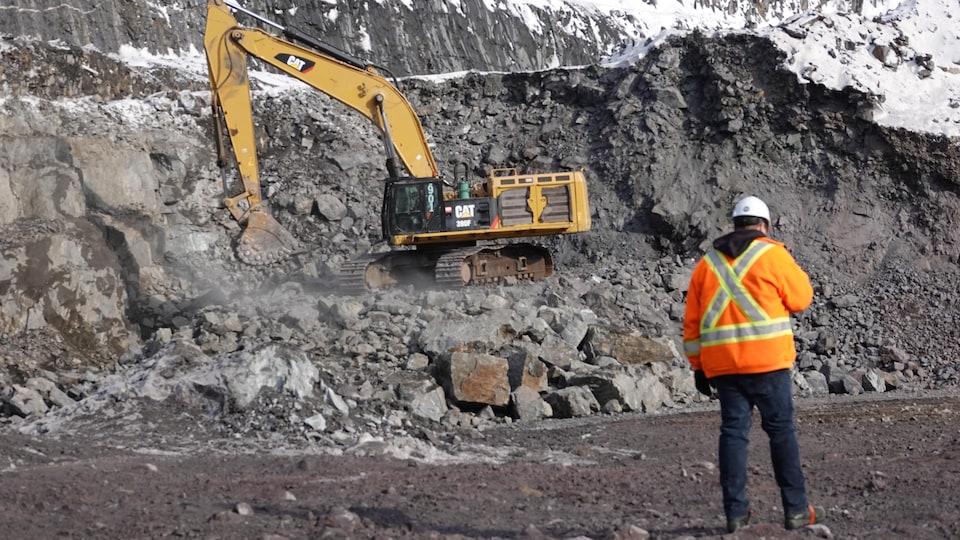 Un travailleur en veste orange se tient debout dans la fosse de la mine. Au deuxième plan, on aperçoit une pelleteuse sur des blocs de roches.