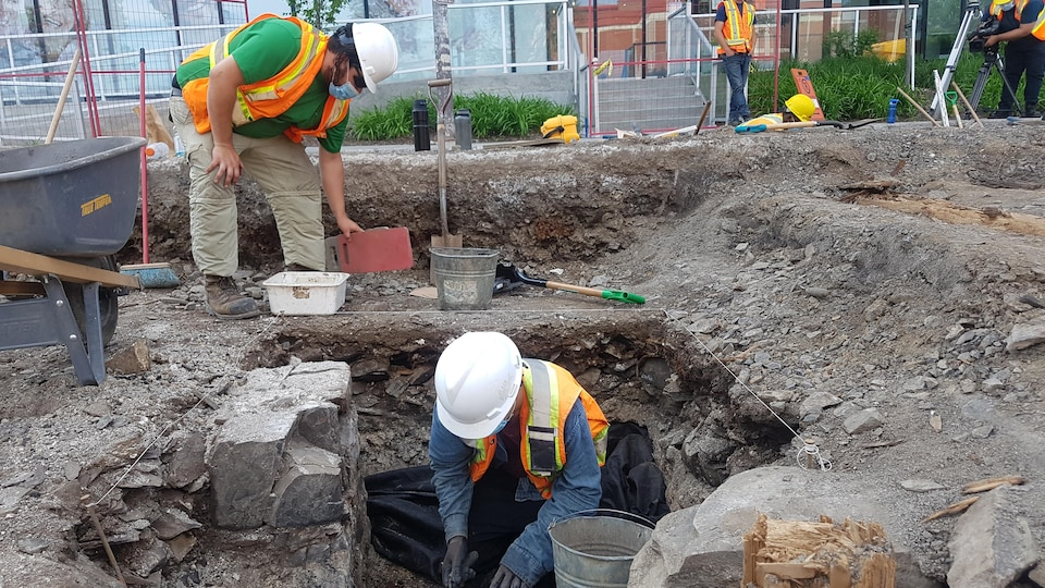 Deux hommes mènent des fouilles sur un site archéologique.