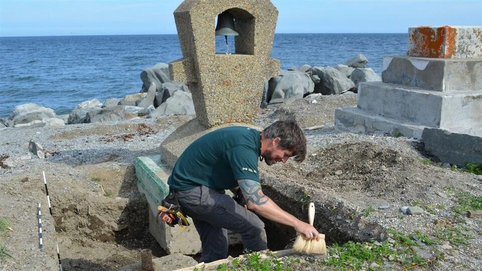 Un homme balaie de la terre à l'aide d'un petit balai près de la cloche du monument.