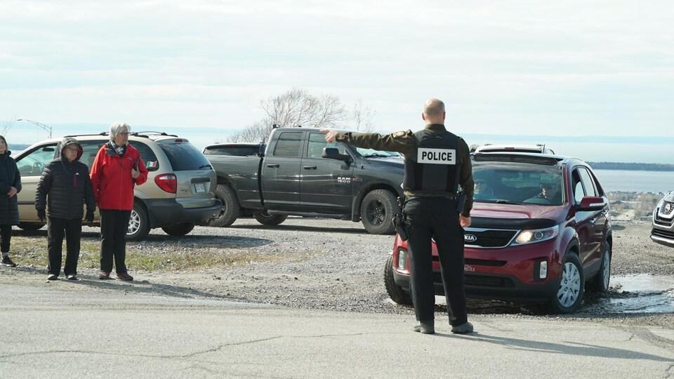 Un policier indique à un conducteur d'aller plus loin.