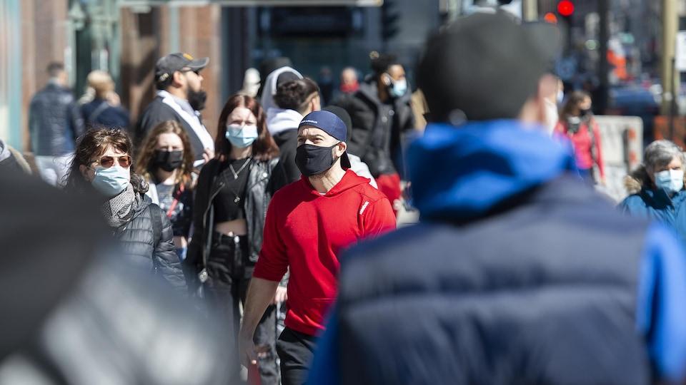 Des gens marchent dans la rue au soleil.