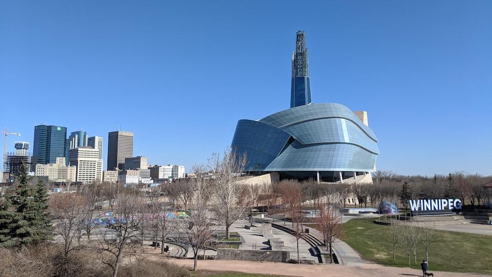 Le musée canadien des droits de la personne vu de l'extérieur, entouré d'espaces verts, avec des bâtiments du centre-ville de Winnipeg en arrière-plan.