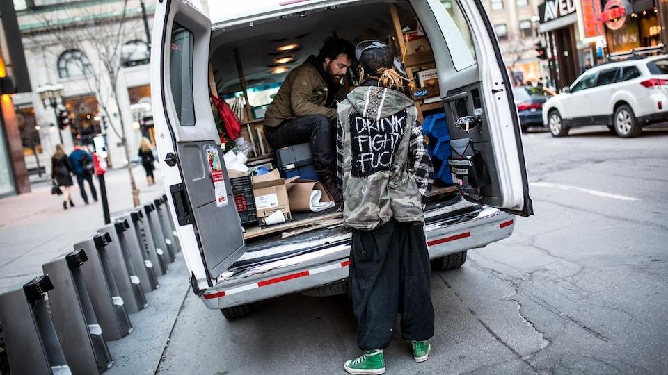 Deux personnes à l'arrière d'une camionnette pleine de livres.