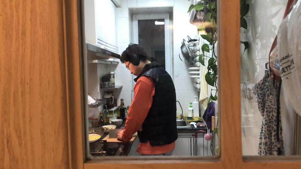 Un homme dans une cuisine coupe des aliments.