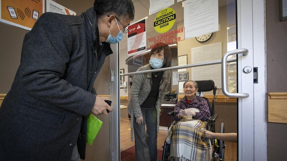 Un homme rend visite à sa mère à travers la porte vitrée du foyer de soins de longue durée Rose of Sharon.