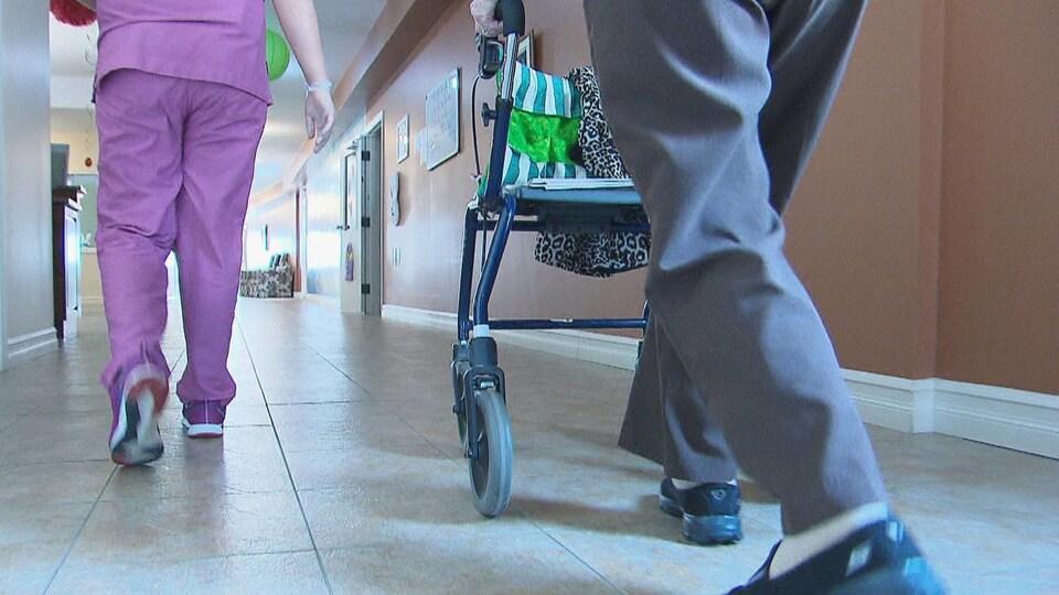 Les jambes d'une employée de foyer de soins et d'un homme poussant une marchette.