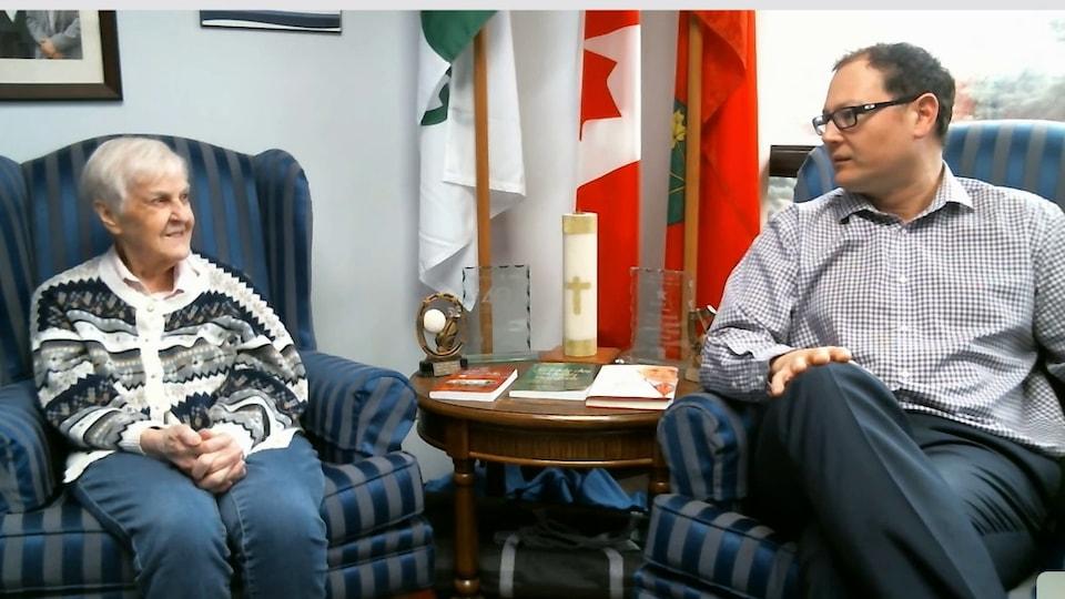 Une capture d'écran d'une conversation vidéo sur Skype. Une femme âgée est assise dans un fauteuil bleu. À côté, un homme est assis dans un fauteuil similaire. Derrière, des drapeaux.