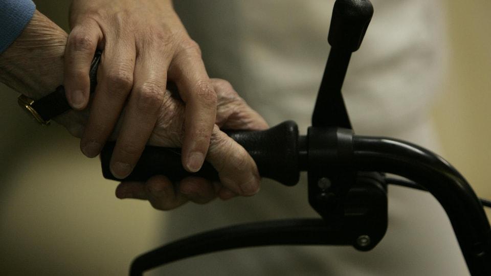 La main d'une infirmière posée sur la main d'une personne âgée pour l'aider à tenir la poignée de sa marchette.