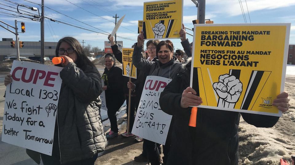 Des manifestants le long de la rue brandissent des pancartes syndicales.
