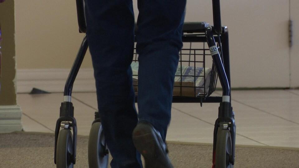 Les jambes et les pieds d'une personne qui avance avec une marchette.