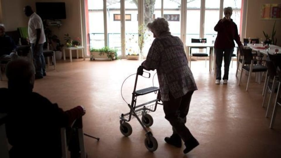 Les silhouettes de deux personnes âgées qui marchent dans un salon