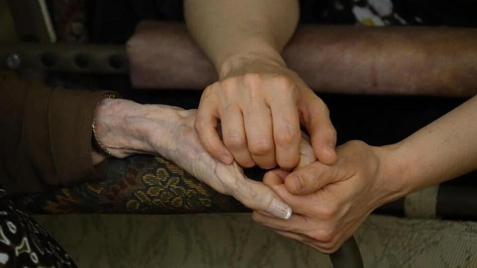 Une femme tient les mains d'une aînée.