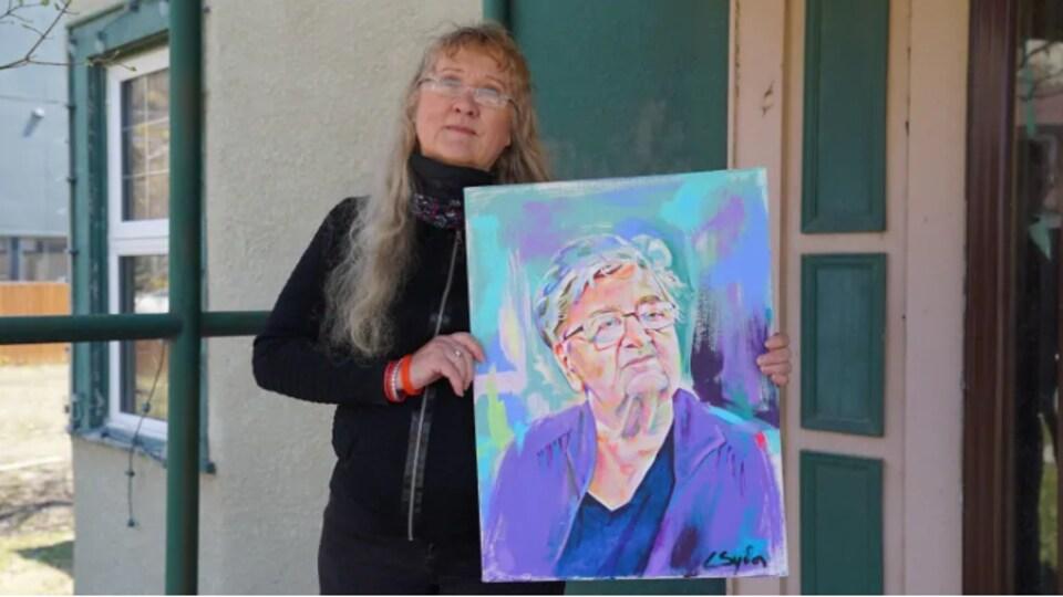 Une femme debout et tenant un portrait de sa mère