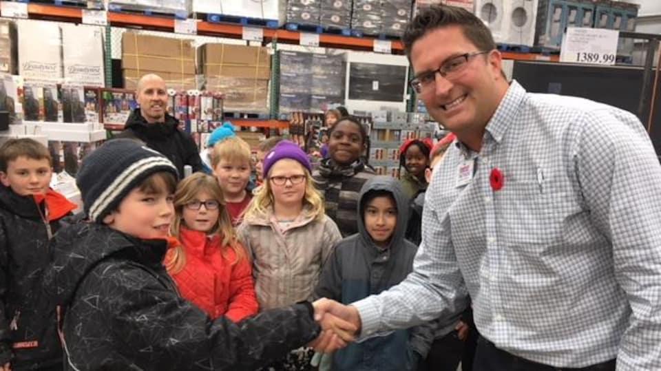 Le gérant serre la main d'un jeune garçon entouré de ses camarades de classe