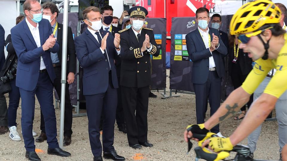 Le président Macron applaudit le cycliste au maillot jaune.