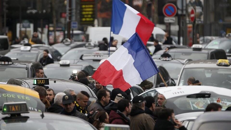 Des manifestants tiennent des drapeaux français entre plusieurs voitures de taxi à l'arrêt.