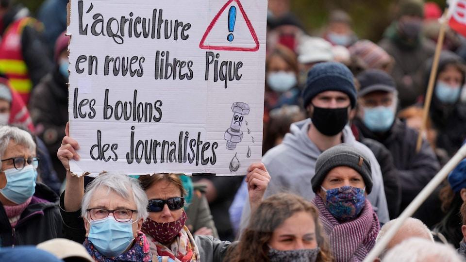 Une affiche sur laquelle est écrit : L'agriculture en roues libres pique les boulons des journalistes.