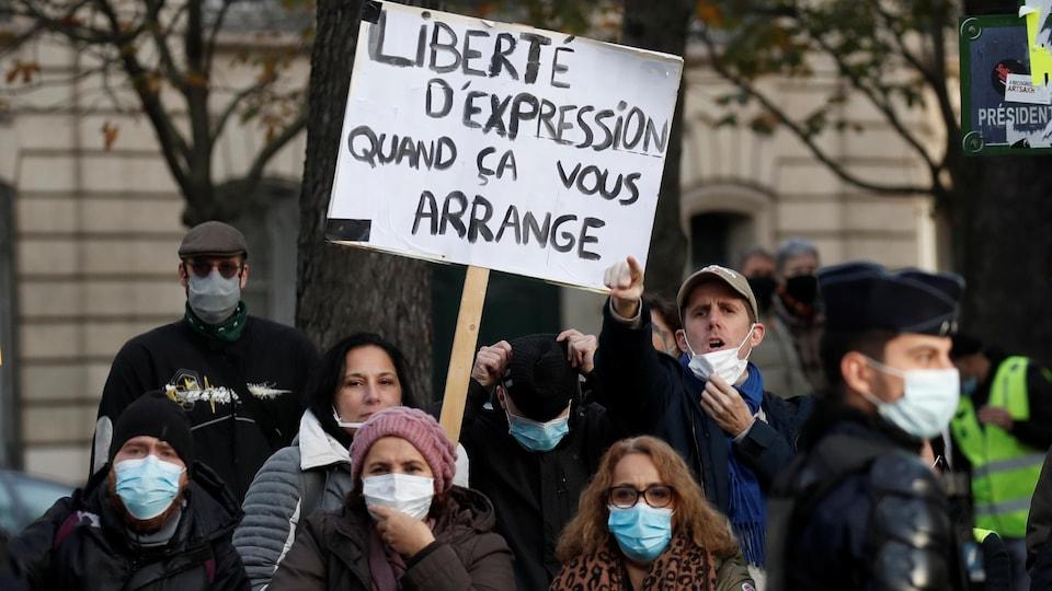 « Liberté d'expression quand ça vous arrange », peut-on lire sur une pancarte brandie par une manifestante entourée de quelques autres personnes derrière des barrières de sécurité.